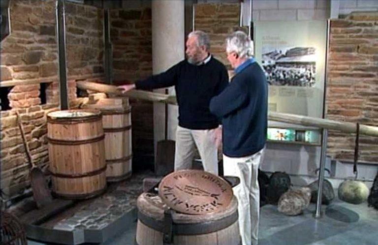 Sir Robin Knox-Johnston demonstrating the pressing of the pilchards to presenter Michael Aspel when the Antiques Roadshow visited the National Maritime Museum in Falmouth (Series 26 Episode 5 broadcast 5/10/2003).